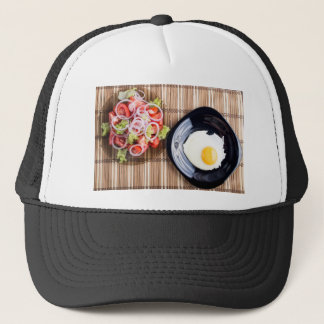 Top view on a fried egg and a salad of tomato trucker hat