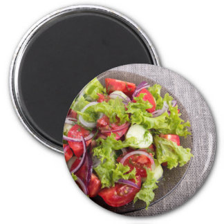 Top view on a plate with fresh salad of raw vegeta magnet