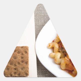 Top view on Cavatappi Pasta on textile background Triangle Sticker