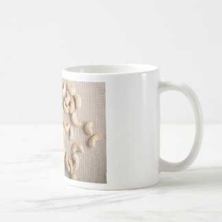 Top view on raw cashew nuts scattered on the table coffee mug