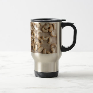 Top view on raw cashew nuts scattered on the table travel mug