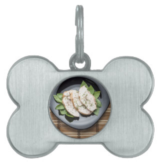 Top view with baked slices of chicken meat pet name tag