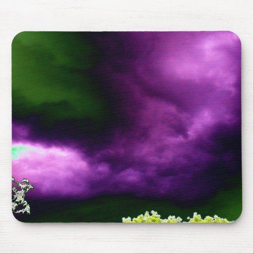 Tormenta verde y púrpura surrealista sobre rama qu mousepads