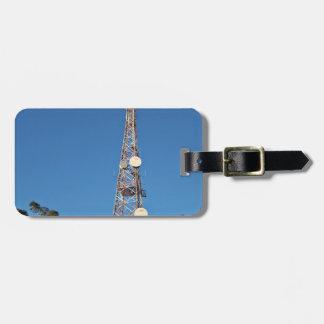 Torre de las telecomunicaciones debajo de un cielo etiquetas de maletas