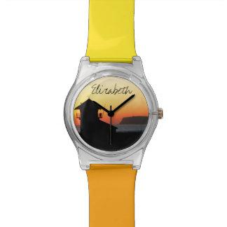 Torre del salvavidas en la puesta del sol con un n relojes de mano