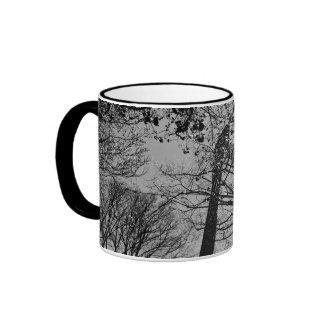 Torre detrás de árboles taza de café