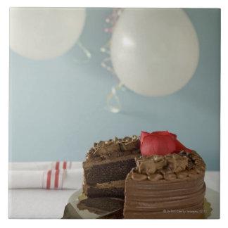 Torta de chocolate con la rebanada que falta en la azulejo cuadrado grande