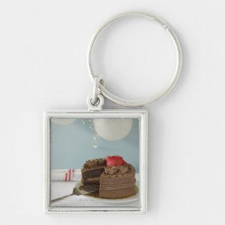 Torta de chocolate con la rebanada que falta en la llavero cuadrado plateado