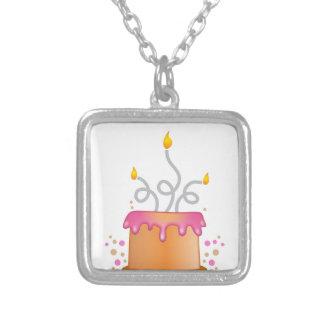 Torta de cumpleaños con las velas twirly rizadas collar plateado