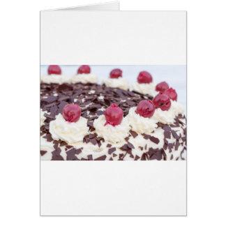 Torta del bosque negro detalladamente con el fondo tarjeta de felicitación