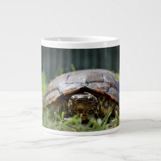 Tortuga de madera adornada en su nivel en hierba taza grande