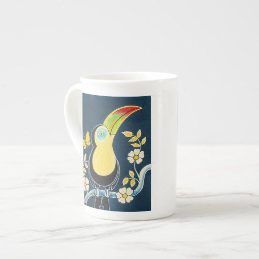 Toucan colorido en el cielo de azules marinos y la taza de porcelana