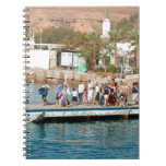 Tourists waiting to climb into a boat spiral note book