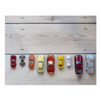 Toy cars lined up in a row on floor post cards
