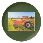 Tractor anaranjado en los campos de granja plato de comida