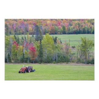 Tractor con la bala de heno en campo verde con fotografía