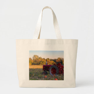 Tractor in a pumpkin field large tote bag