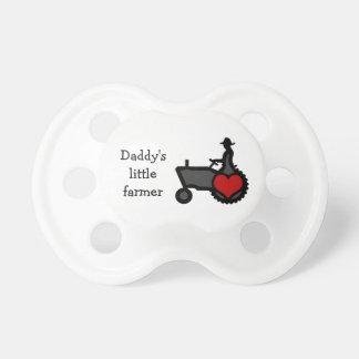 Tractor lindo del pequeño bebé del granjero con el chupete de bebe