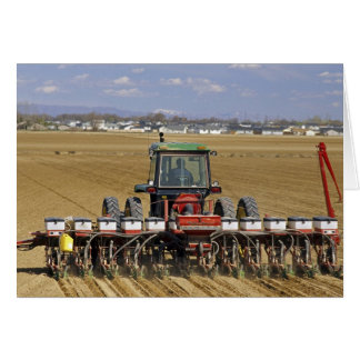 Tractor pulling a seed corn planter. card