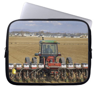 Tractor pulling a seed corn planter. computer sleeve