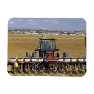 Tractor pulling a seed corn planter. magnet