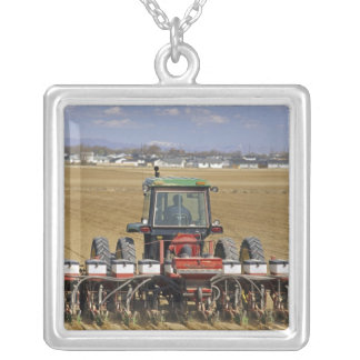 Tractor pulling a seed corn planter. silver plated necklace