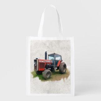 Tractor rojo de Massey Ferguson en el campo Bolsas Reutilizables