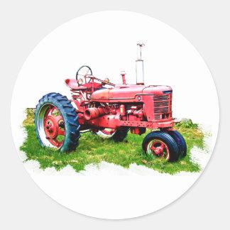 Tractor rojo del vintage en el campo etiqueta redonda