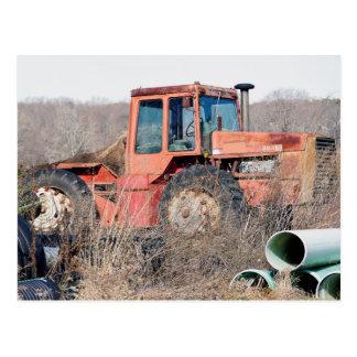 Tractor rojo grande viejo abandonado que tarjetas postales