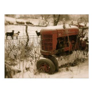 Tractor rojo viejo con la postal del navidad de la