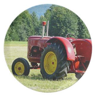 Tractor rojo y amarillo antiguo en campo platos para fiestas
