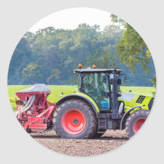 Tractor with agricultural machine on land.JPG Classic Round Sticker