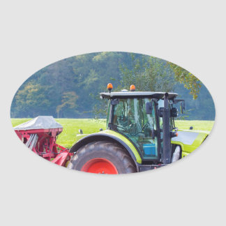 Tractor with agricultural machine on land.JPG Oval Sticker