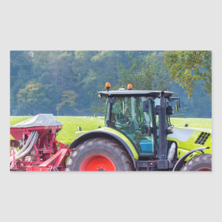 Tractor with agricultural machine on land.JPG Rectangular Sticker