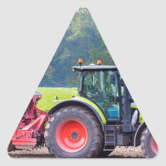 Tractor with agricultural machine on land.JPG Triangle Sticker