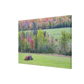 Tractor with hay bale in green field with canvas print