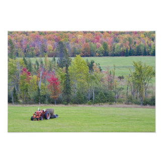 Tractor with hay bale in green field with photo print
