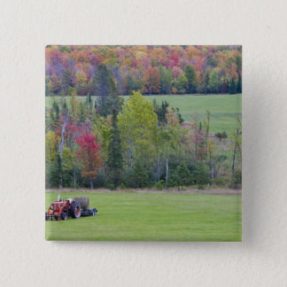 Tractor with hay bale in green field with pinback button