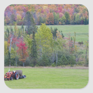 Tractor with hay bale in green field with square sticker