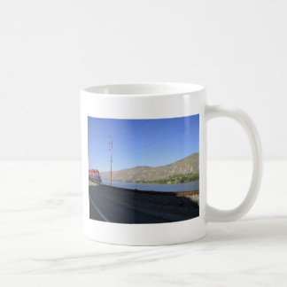 Train on tracks along water coffee mug