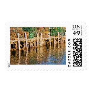 Trampas de la langosta apiladas en el embarcadero sellos