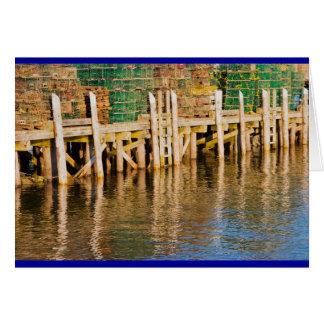 Trampas de la langosta apiladas en el embarcadero tarjeton