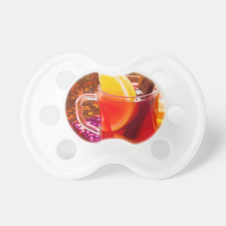 Transparent cup of tea with citrus, cinnamon pacifier