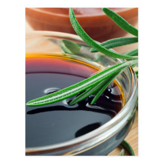 Transparent cup with soy sauce and rosemary leaves postcard