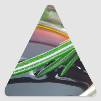 Transparent cup with soy sauce and rosemary leaves triangle sticker