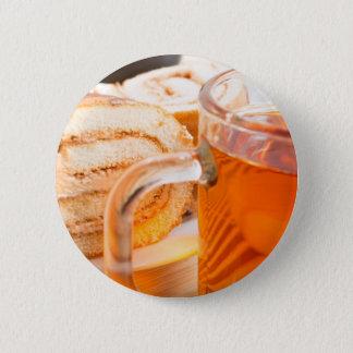 Transparent glass mug with hot tea and chocolate button