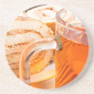 Transparent glass mug with hot tea and chocolate sandstone coaster
