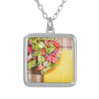 Transparent plate with fresh summer salad on a mat silver plated necklace