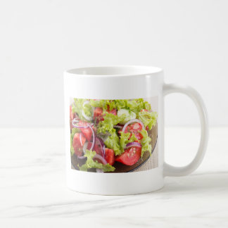 Transparent plate with vegetable salad closeup coffee mug