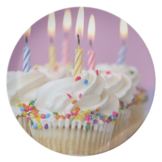 Tray of birthday cupcakes with candles dinner plate